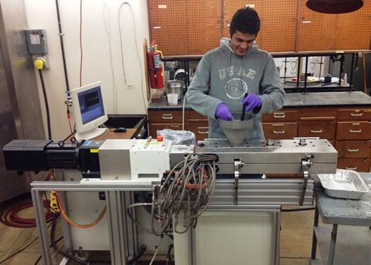 A student demonstrates extrusion equipment at the IAPC lab